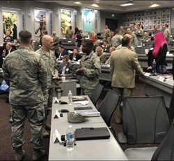 Here, Katie is taking part in a roundtable on a military base, her pink hair amongst a sea of camouflage. Photo credit: Wade Barker